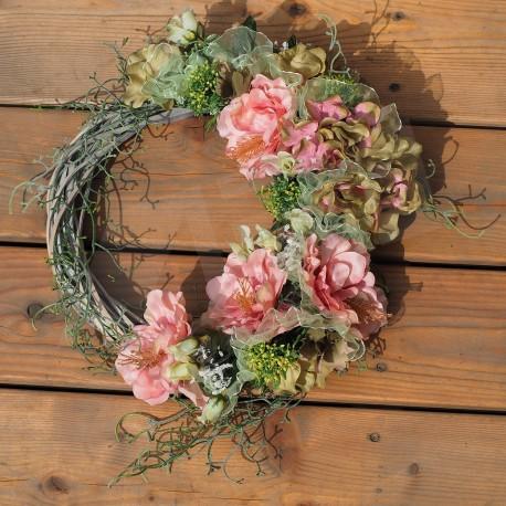 věnec na šedém proutěném základu, látkové květy hortenzie a ibišku, doplněny lístky, bobulemi  a zelenkavou tylovou stuhou