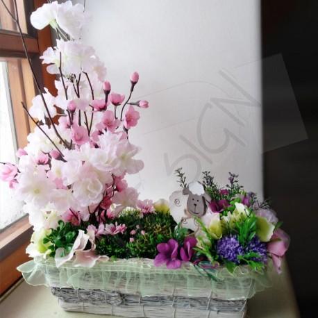 proutěný patinovaný košík, doplněný zelenkavou stuhou, aranžovaný umělými něžně růžovými květy sakury,doplněno kvítky v pastelov