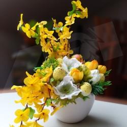 bílá keramická nádoba ve tvaru skořápky, aranžována bílými a žlutými jarními květy, doplněno hnízdečkem s kuřátky a velikonočním