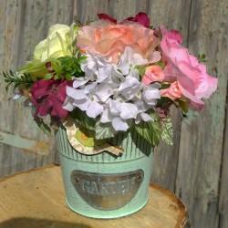 plecháček v zelenkavé barvě, aranžovaný látkovými květy růží v tónech růžovo-vínové barvy, doplněno umělou zelení