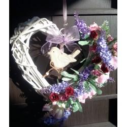 proutěné bílé srdíčko s dřevěným ptáčkem, aranžováno umělými kvítky levandule, doplněno vínovo-růžovými květy minirůžiček
