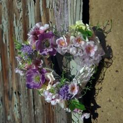 bílé proutěné srdíčko  zdobené jarními látkovými květy   v odstínech růžové a fialové  doplněno umělou zelení  dekorace vhodná d