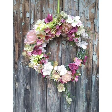 dekorace vhodná k zavěšení  proutěný patinovaný základ  aranžovaný látkovými květy hortenzie v tlumených barvách  doplněno květy