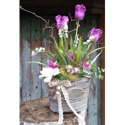 proutěný košík v šedé barvě   zdobený látkovými květy tulipánů a konvalinek,  doplněno květy krokusů, umělou zelení  a hnízdečke