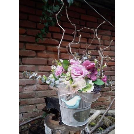 plechová nádoba v barvě bílé kávy  zdobená látkovými květy růží a hortenzií  doplněno umělou zelení  a keramickým ptáčkem v zele