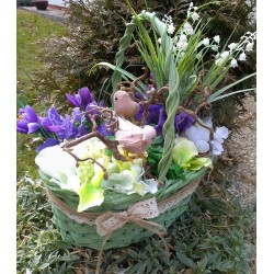 proutěný zelenkavý košík aranžovaný umělými  jarními květy konvalinek a krokusů  doplněno větvičkami kroucené lísky,  ptáčky