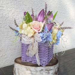 proutěný čtvercový košík ve fialovém odstínu  bohatě aranžovaný látkovými květy tulipánů, hortenzií, růžiček