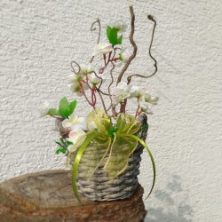 drobný proutěný košík  s jarním aranžmá  umělé větvičky rozkvetlé třešně,   doplněno větvičkami lísky a hnízdečkem