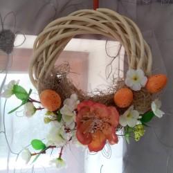 proutěný věneček v přírodním odstínu  aranžován v oranžovém tónu látkovými květy a velikonočními vajíčky