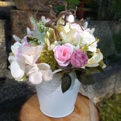 nádoba v bílé barvě   aranžována látkovými květy růží a minirůžiček, květy hortentie v pastelových tónech