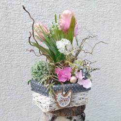 proutěný košík v bílé barvě, plný jarních látkových květů, tulipány, konvalinky, kalina