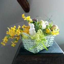 proutěný košík v zelenkavé barvě, aranžovaný jarními květy a umělou zelení, dekorace doplněna keramickým zajíčkem a vajíčky