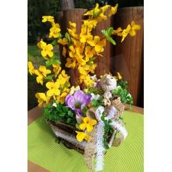 přírodní proutěný košík zdobený jutou a krajkou, větvičky zlatého deště, fialové květy sasanek, doplněno keramickou ovečkou